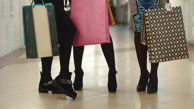Όμορφα πόδια γυναικών ` s μετά από να ψωνίσει Τα κορίτσια έχουν τις τσάντες εγγράφου στα χέρια τους Δύο γυναίκες στα υψηλά τακούν απόθεμα βίντεο