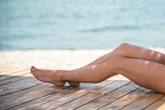 Όμορφα πόδια γυναικών ` s στην παραλία Στοκ Εικόνες