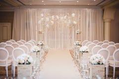 Όμορφα στοιχεία διακοσμήσεων σχεδίου γαμήλιας τελετής με την αψίδα, floral σχέδιο, λουλούδια, καρέκλες Στοκ Εικόνα
