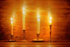 Όμορφα τέσσερα κεριά με τα διαφορετικά εκλεκτής ποιότητας κηροπήγια στο wo Στοκ Φωτογραφία