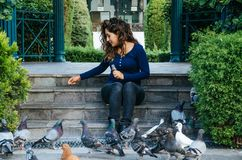 Όμορφα ταΐζοντας περιστέρια γυναικών χαμόγελου στο πάρκο κατά τη διάρκεια της ημέρας στοκ εικόνες