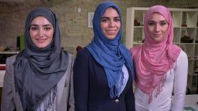Όμορφα τρία αραβικά κορίτσια hijab στέκονται μαζί ψυχρά με τα βέβαια πρόσωπα χαμόγελου, η κάμερα που συγκεντρώνεται κοιτάζει απόθεμα βίντεο