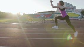 Όμορφα τραίνα κοριτσιών ικανότητας στο στάδιο Ένας νέος αθλητής τρέχει τα εμπόδια φιλμ μικρού μήκους