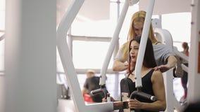 Όμορφα τραίνα brunette σκληρά στον εκπαιδευτή του σφυριού κάτω από την καθοδήγηση του λεωφορείου απόθεμα βίντεο