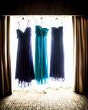 Όμορφα φορέματα παράνυμφων πορφύρας και κιρκιριών που κρεμούν σε ένα παράθυρο Στοκ Φωτογραφία