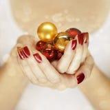 Όμορφα χέρια γυναικών που κρατούν τις διακοσμήσεις Χριστουγέννων Στοκ Φωτογραφία