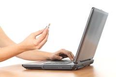 Όμορφα χέρια γυναικών σε ένα lap-top με έναν ρυθμιστή πεννών Στοκ Εικόνα