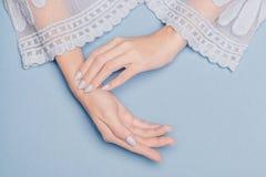 Όμορφα χέρια με τα μπλε καρφιά σε ένα μπλε υπόβαθρο στοκ φωτογραφία με δικαίωμα ελεύθερης χρήσης