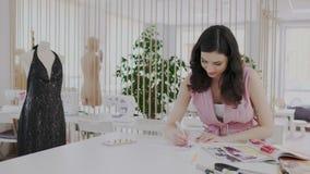 Όμορφα χαμογελώντας σκίτσα σχεδίων μοδιστρών μόδας ή δημιουργών υφασμάτων στο εργαστήριο φωτός της ημέρας Seamstress χρώματα απόθεμα βίντεο