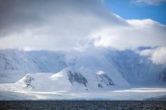 Όμορφα χιονοσκεπή βουνά της Ανταρκτικής τοπίων ενάντια στον ουρανό σύννεφων Στοκ Εικόνες