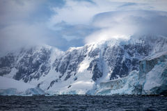 Όμορφα χιονοσκεπή βουνά της Ανταρκτικής τοπίων ενάντια στον ουρανό σύννεφων Στοκ Φωτογραφία