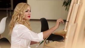 Όμορφα χρώματα καλλιτεχνών κοριτσιών στη ζωγραφική καμβά easel τέχνη απόθεμα βίντεο