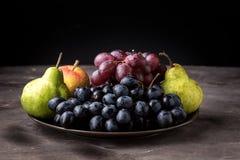 Όμορφα ώριμα φρούτα πιάτων της Apple αχλαδιών και σταφυλιών στα σκοτεινά εποχιακά φρούτα φθινοπώρου υποβάθρου φωτογραφιών σκοτειν Στοκ Φωτογραφίες