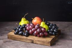 Όμορφα ώριμα φρούτα στα ξύλινα δίσκων της Apple αχλαδιών και σταφυλιών σκοτεινά εποχιακά φρούτα φθινοπώρου υποβάθρου φωτογραφιών  Στοκ Φωτογραφία