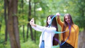 Όμορφα gymnast κοριτσιών τραίνα ευτυχώς στο πάρκο το καλοκαίρι με μια μπλε κορδέλλα απόθεμα βίντεο
