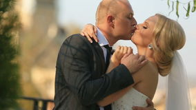 Όμορφα newlyweds που φιλούν μαλακά στο υπόβαθρο εκκλησιών απόθεμα βίντεο