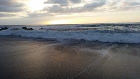 Όμορφα sunsets στη μαύρη παραλία 24 άμμου Στοκ Εικόνα