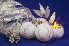 Όμορφες άσπρες σφαίρες έτους ` s γυαλιού νέες με ένα ασημένιο σχέδιο, άσπρο λαμπρό tinsel, κώνος σε ένα μπλε υπόβαθρο - νέο compo Στοκ Εικόνες