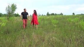 Όμορφες άτομο και έγκυος γυναίκα ζευγών με μακρυμάλλη σε ένα κόκκινο φόρεμα Οικογένεια φιλμ μικρού μήκους
