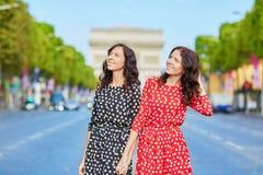 Όμορφες δίδυμες αδελφές μπροστά από Arc de Triomphe Στοκ Εικόνες