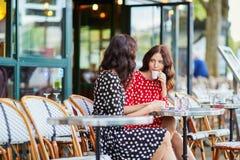 Όμορφες δίδυμες αδελφές που πίνουν τον καφέ Στοκ Εικόνες