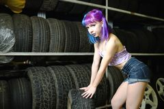 Όμορφες αυτοκινητικές μηχανικές εργασίες κοριτσιών hipster με τις ρόδες στις ρόδες Στοκ Εικόνες