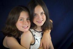 Όμορφες αδελφές που χαμογελούν και που αγκαλιάζουν Στοκ Φωτογραφία