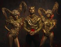 Όμορφες γυναίκες διαβόλων με τα χρυσά διακοσμητικά κέρατα και όμορφος άνδρας διαβόλων στο διακοσμητικό σακάκι στοκ εικόνες με δικαίωμα ελεύθερης χρήσης