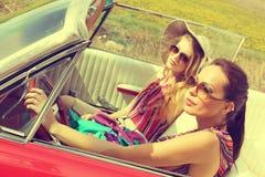 Όμορφες γυναίκες που οδηγούν έναν κόκκινο αναδρομικό τρύγο αυτοκινήτων που φορά accesoriess Στοκ Φωτογραφίες