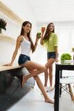 Όμορφες γυναίκες που πίνουν το φρέσκο χυμό Detox για την υγιή διατροφή στοκ εικόνες