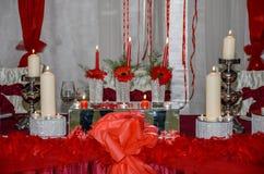 Όμορφες διακοσμήσεις κεριών με τις κόκκινες κορδέλλες στη γαμήλια ετικέττα Στοκ Εικόνα