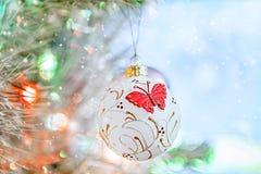 Όμορφες διακοσμήσεις Χριστουγέννων υπό μορφή άσπρης σφαίρας χιονιού με μια κόκκινη πεταλούδα στοκ φωτογραφία με δικαίωμα ελεύθερης χρήσης