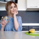 Όμορφες ενάρξεις κοριτσιών το πρωί της με ένα ποτήρι του νερού με το λεμόνι Στοκ φωτογραφία με δικαίωμα ελεύθερης χρήσης