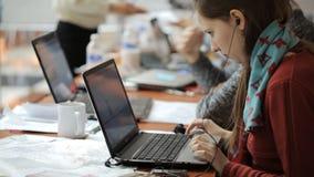 Όμορφες εργασίες γυναικών για το lap-top στο γραφείο που ακούει τη μουσική απόθεμα βίντεο