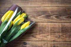 Όμορφες κίτρινες τουλίπες στη συσκευασία σε ένα ξύλινο υπόβαθρο στοκ φωτογραφία