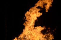 Όμορφες καυτές καίγοντας ψηλές φλόγες από τη φωτιά στο σκοτεινό χειμερινό υπόβαθρο Στοκ Φωτογραφίες