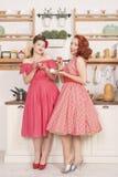Όμορφες κομψές αναδρομικές γυναίκες που στέκονται στην κουζίνα και το χαμόγελό τους στοκ εικόνες