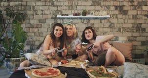 Όμορφες κυρίες που παίζουν σε ένα παιχνίδι PlayStation στη νύχτα sleepover που τρώει την πίτσα και που ξοδεύει έναν καλό χρόνο μα φιλμ μικρού μήκους