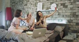 Όμορφες κυρίες που παίρνουν selfies στο κόμμα sleepover σε μια σύγχρονη κρεβατοκάμαρα που φορά μια όμορφη πυτζάμα και που ξοδεύει φιλμ μικρού μήκους