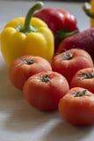 Όμορφες κόκκινες ντομάτες στο μετρητή κουζινών με άλλο vegetab Στοκ Φωτογραφίες