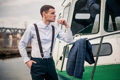 Όμορφες νέες αρσενικές στάσεις επιχειρηματιών στην αποβάθρα στο σταθμό βαρκών στοκ φωτογραφία