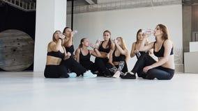 Όμορφες νέες γυναίκες ικανότητας στα μαύρα ενδύματα που κάθονται στο πάτωμα και το πόσιμο νερό μετά από την ικανότητα στην αίθουσ απόθεμα βίντεο