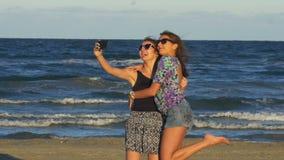 Όμορφες νέες γυναίκες που έχουν μια τηλεοπτική συνομιλία κλήσης στην παραλία απόθεμα βίντεο