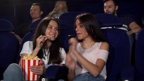 Όμορφες νέες γυναίκες που απολαμβάνουν προσέχοντας τους κινηματογράφους στον κινηματογράφο φιλμ μικρού μήκους