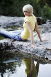 Όμορφες νέες γυναίκες που χαλαρώνουν κοντά σε μια λίμνη βράχου στοκ εικόνα με δικαίωμα ελεύθερης χρήσης