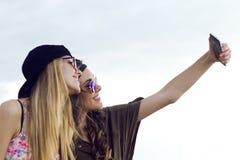 Όμορφες νέες γυναίκες που χρησιμοποιούν το κινητό τηλέφωνο στην οδό Στοκ Εικόνα