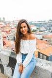 Όμορφες νέες ενήλικες γυναίκες που θέτουν στο πανόραμα πόλεων οριζόντων του Πόρτο στο υπόβαθρο Στοκ Φωτογραφίες
