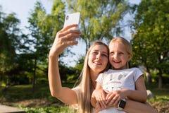 Όμορφες νέες μητέρα και κόρη με την ξανθή τρίχα που χρησιμοποιεί το κινητό τηλέφωνο υπαίθριο Μοντέρνα κορίτσια που κάνουν selfie  στοκ εικόνες με δικαίωμα ελεύθερης χρήσης