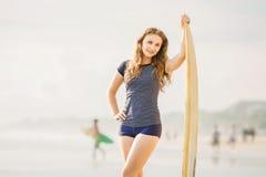 Όμορφες νέες παραμονές κοριτσιών surfer στην παραλία Στοκ Εικόνες