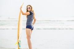Όμορφες νέες παραμονές κοριτσιών surfer στην παραλία Στοκ Φωτογραφίες